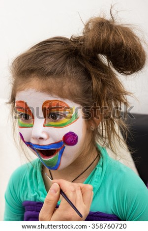 A girl is painted by someone as a clown - stock photo