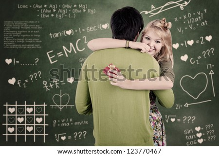 A girl is smiling because he gets a present from her boyfriend in classroom