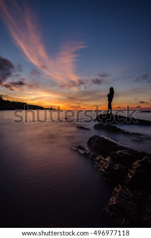 A girl is stand and looking to the sunset in Lake Superior