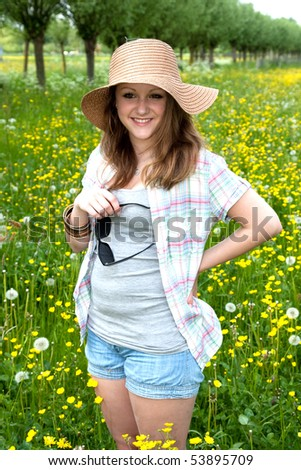 A girl is standing in a field of grass and flowers with her sunglasses