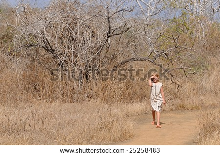 A girl is walking the galapagos forest, looking around for the rare birds - stock photo