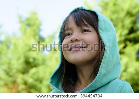 a girl is watching far away and smiling.