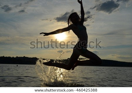 A girl jumping on the riverside