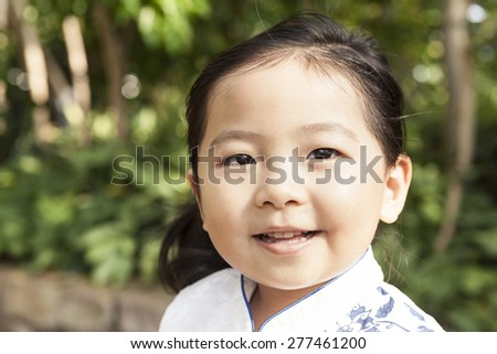 A girl(kid) wearing Chinese traditional clothes(dress, chipao) with big smile in the botanical garden at the spring,  - stock photo