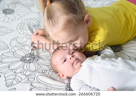 A girl kissing her younger three month old sister lying on a bed. - stock photo