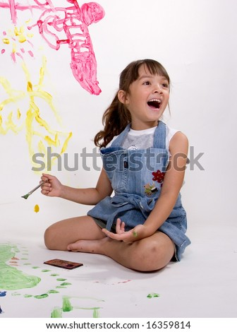 A girl laughs while paiting pictures. - stock photo