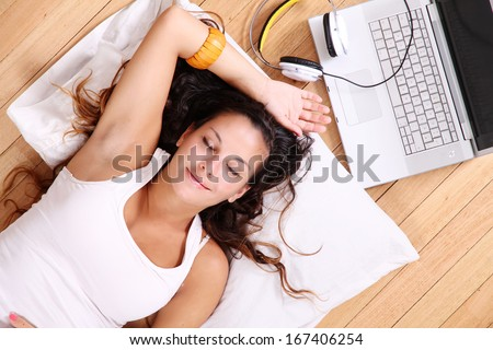 A girl laying on the Floor after surfing on the Internet with a Laptop. - stock photo