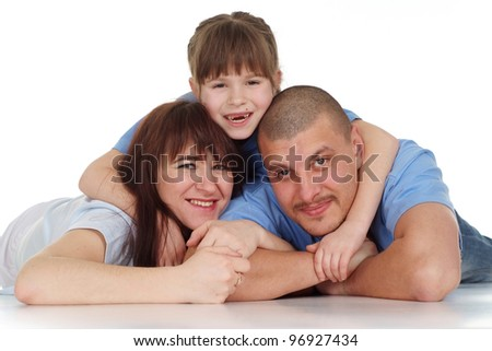 A girl lies on top of his parents on a white background
