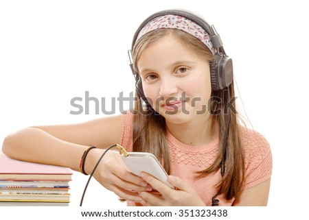 a girl listening wireless music with headphones from smart phone on white - stock photo