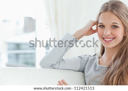 A girl looking at the camera as she smiles with her hand on her head