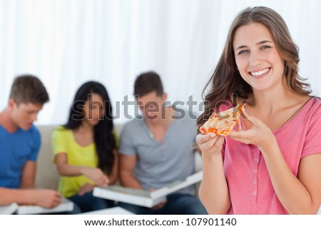 A girl looking at the camera smiling as she holds a slice of pizza in front of her friends - stock photo