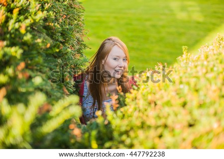 A girl looks out of bushes near the castle in the Czech Republic