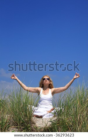 A girl meditating on sand dunes in yoga position - stock photo