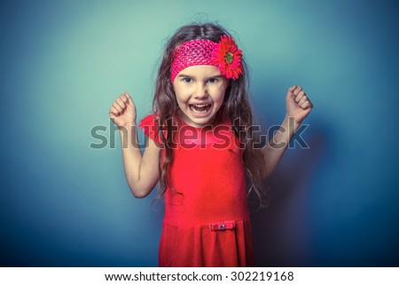 a girl of seven European appearance brunette in a bright dress clenched fists shouting on gray background, anger, rage, scream retro photo effect - stock photo