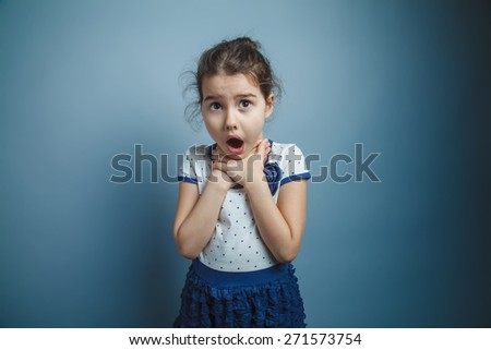 a girl of seven European appearance brunette opened her mouth keeps his hands by the throat on a gray background, choke - stock photo