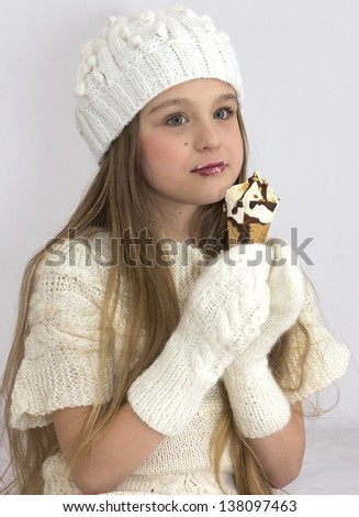 A girl of 9 years in a white dress with ice-cream