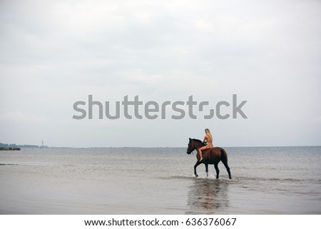 a girl on horseback rides along the coast