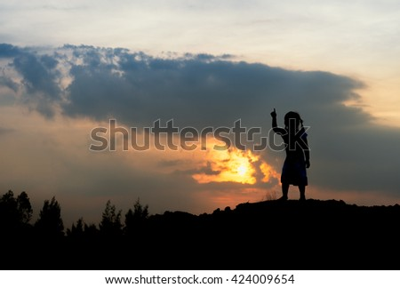 A girl playing on a the hill at sunset,silhouette concept.