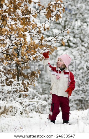 A girl playing with snow on a tree