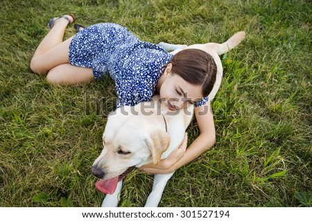 A girl plays with a dog on the grass. Training the dog, the performance of the teams. - stock photo