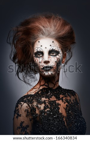 A girl posing in a creepy halloween costume of a witch with peircing and cracked painted face. - stock photo