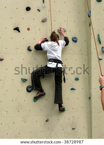 A girl practicing climbing skills on a climbing wall - stock photo