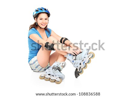 A girl putting on roller skates isolated against white background