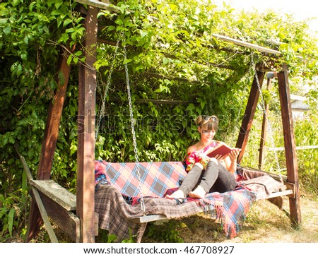 A girl reads a book in the garden on a swing.