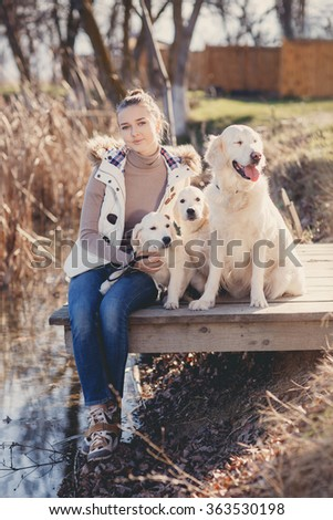 A girl rests with the dog by the river. Beautiful woman playing with her dog. Outdoor portrait.Portrait of a woman with her beautiful dog lying outdoors - stock photo