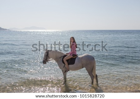 A girl riding a horse by the sea