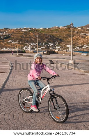 A  girl riding her bicycle in spring. - stock photo