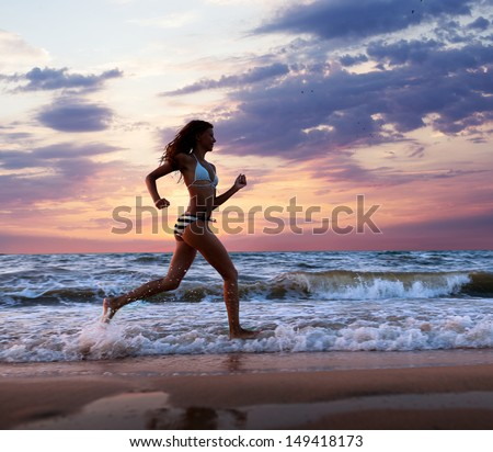 A girl runs along the beach