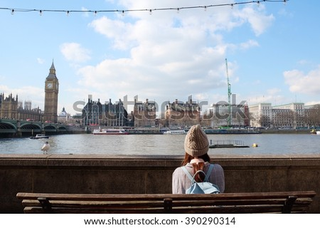 A girl 's sitting beside Thames river, watching London city Big Ben and Westminster bridge - stock photo