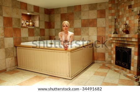 A girl sits in the bathroom. Tiles. Bath. Sexy look. Near a fireplace. - stock photo