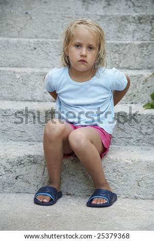A girl sits on a stone staircase in a blue T-shirt