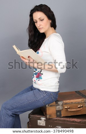 A girl sits on an old suitcase and reading a book. The girl in jeans and a white sweater. - stock photo