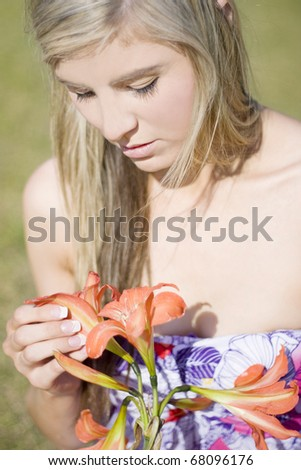 A Girl Sitting In A Grassy Meadow Pulls Petals Off A Flower Whilst Chanting He Loves Me He Loves Me Not - stock photo