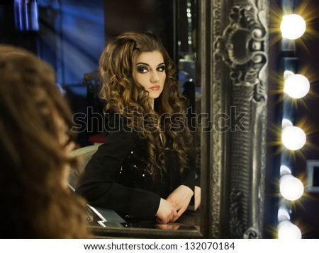 A girl sitting in front of a  mirror . Young witch 	 	 	 	 	 	 	 	 	 	 	 A young girl sitting in front of a big mirror and looking away of her reflection, mirror stage concept shot - stock photo