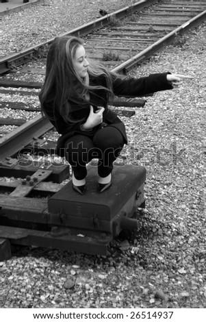A girl sitting near railroad - stock photo