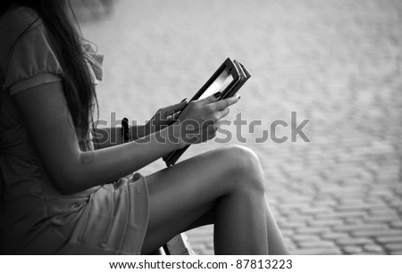 A girl sitting on a bench and reading a book (black white) - stock photo