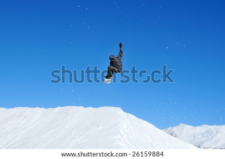 a girl snowboarder takes off from a jump and reaches for the sky with her right arm