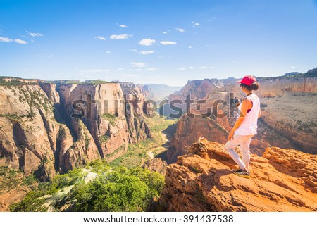 A Girl Standing at The Edge of The Cliff in Zion National Park, USA - stock photo