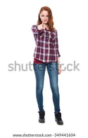 A girl standing in full length confident shows a finger at the camera. Young woman in checkered shirt and blue jeans isolated on a white background - stock photo