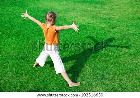 a girl standing on the grass  looking at his shadow - stock photo