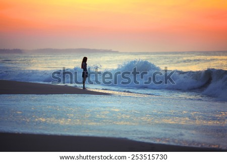 A girl stands  at dusk on the shore of stormy ocean