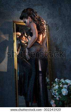 A girl stands near the mirror, trying on dress - stock photo