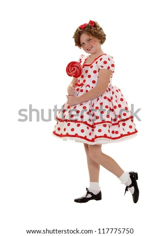 A girl stands with a red lollipop in a polka dot dress isolated on white - stock photo