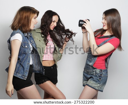 A girl takes picture of her friends. Concept of friendship and fun.Best friends enjoying the moment with modern camera. - stock photo