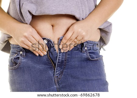 A girl tries to squeeze into jeans that are too tight. - stock photo