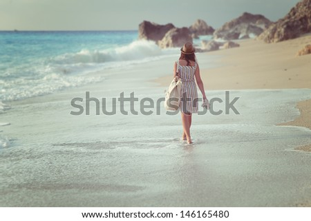 A girl walking on a beach  - stock photo